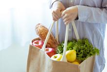 エコバッグに入った野菜やパンを持つ女性の手元