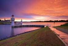 A Dramatic Sunset Over An Inland River With Two Lighthouse Beacons