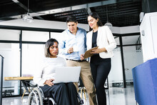 Mexican Disabled Transgender Businesswoman Holding A Laptop With Another Businesswoman Taking Notes And Office Colleague Holding A Cup Of Coffee In The Office, In Disability Concept And Disabled Peopl