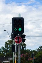 Traffic Light With Green Arrow And Stop Sign At City Intersection