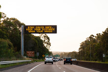 Digital Sign Above Road Warning About Covid-19 Safety Stay Covid Safe Keep Your Distance Wash Hands