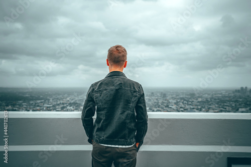 Fotografia A young man enjoys a view of the city from the observation deck at the Griffith