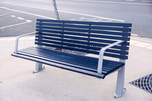 An Empty Blue Bench On A Street Corner Waiting For Tired Pedestrians To Sit Down.