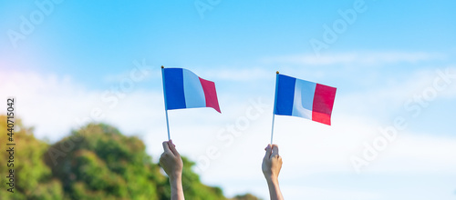 Obraz na plátne hand holding France flag on blue sky background