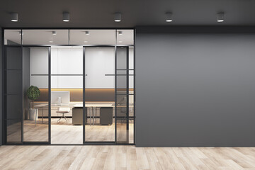 Black wall with copyspace for your text or logo next to doors to sunny office with monochrome style interior design, modern laptops on white tables and wooden floor. 3D rendering, mockup