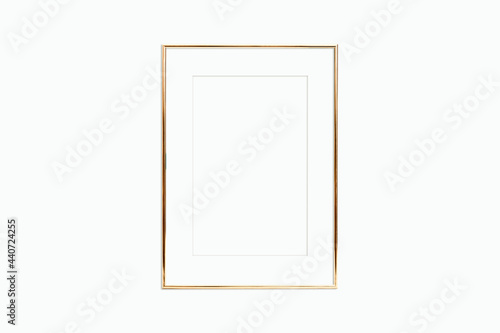 Fotografering Thin gold frame with mat on a white wall