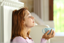 Woman Relaxing On Radiator Holding Coffee Cup
