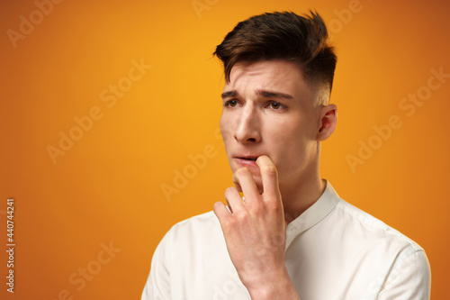 Fototapeta Frustrated and nervous young man biting nail against yellow background