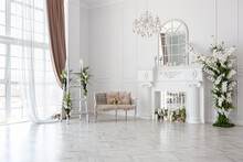 Luxurious Bright Spacious Guest Room With Beautiful Chic Furniture A Huge Floor-to-ceiling Window In A Royal Style Is Decorated With Green Plants, White Walls With Stucco And A Fireplace