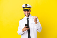 Airplane Caucasian Pilot Isolated On Yellow Background With Phone In Victory Position