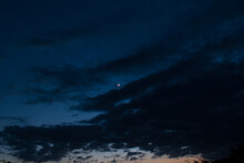 Silhouette Picture Of Dark Cloudy Blue Sky And Waxing Crescent Moon In Middle