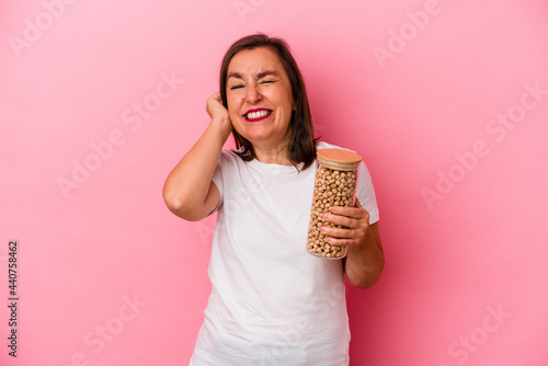 Obraz na plátně Middle age caucasian man holding a chickpeas jar isolated on pink background covering ears with hands