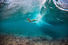 Beautiful Woman In The Bikini Doing Duck Dive With The Surfboard Under The Breaking Waves In The Clear Water Of The Indian Ocean