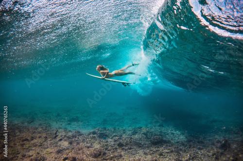 beautiful woman in the bikini doing duck dive with the surfboard under the break Fototapeta