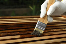 Worker Applying Wood Stain Onto Planks Outdoors, Closeup