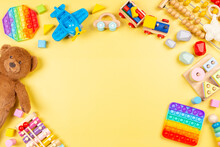 Baby Kids Toy Background With Teddy Bear, Wooden And Musical Toys, Abacus, Plane, Pop It Fidget Toys And Colorful Blocks On Yellow Background. Top View, Flat Lay