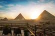 Great Pyramids of Chephren Khafra and Cheops Khufu and Mikerina Menkaura. Sunset on Giza plateau. sun sets below horizon. rooftop restaurant in Cairo with beautiful view of landmark. Cairo, Egypt.