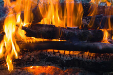 Firewood, Stacked And Burning In The Fire With An Orange Flame With The Formation Of Ash, Below Are Red Coals. A Cozy Picture Of A Comfortable Warming Fire In A Camping Camp.