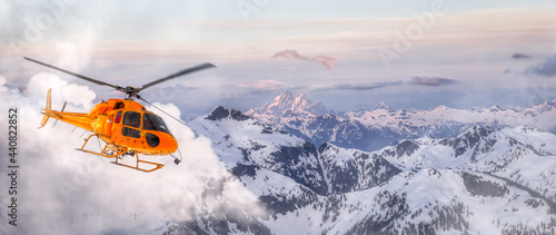 Fotografija Yellow Helicopter flying over the Rocky Mountains during a sunny sunset