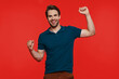 Leinwandbild Motiv Happy young man in casual wear looking at camera and gesturing while standing against red background