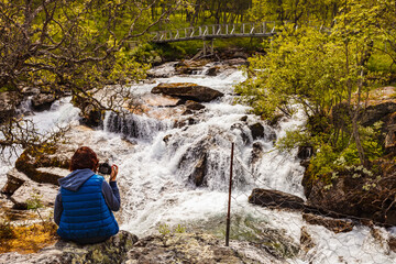Tourist with camera at river, Norway