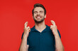 Leinwandbild Motiv Cheerful young man in casual wear keeping fingers crossed while standing against red background