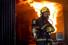 Firefighter Man With Protective And Safety Clothes Stand With Arm-crossed In Front Of Fire On Wall And Ceiling In The Kitchen.