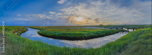 Fotografie, Obraz Panorama of salt marsh, mud flat and bridge over marsh channel in Sankt Peter Ording at the Südstrand