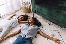 Mother And Daughter Pretending To Be Asleep On Floor