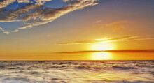 Beautiful View Of The Wavy Ocean Gleaming Under The Sunrays On The Horizon
