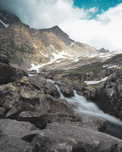 Vertical Shot Of A Stream On A Mountain On A Cloudy Day