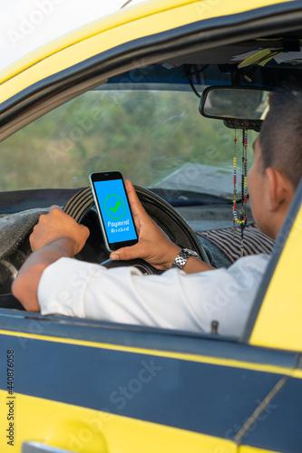 Valokuvatapetti Hispanic man checking his cell phone while driving a yellow car