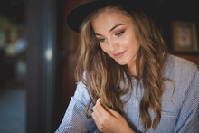 Shallow Focus Shot Of Beautiful Bosnian Blonde Woman Wearing Hat In A Cafea