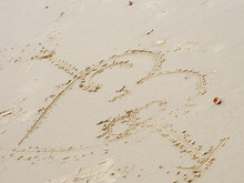 An Arrow With A Heart Through It Drawn In The Sand