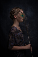 Profile Portrait Of A Woman With A Peacock Feather Hiding Her Eye