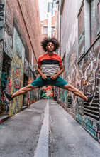 A Young African Afro Is Making An Acrobatic Jump On The Street Opening His Legs In The Air.