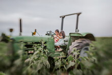 Two Little Girls On A Green Tractor