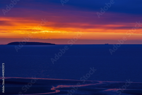 Sunset over the Irish Sea from Penmaenmawr, Wales with a silhouette containers ship on the horizon Fototapet