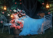 Fantasy Woman Sleeping Beauty Lies Sleep On Comfortable Bed, Mattress, Soft Pillow. Background Mystical Garden, Night, Peonies Flowers Green Trees. Fairy-tale Girl Princess In Blue Dress. Sweet Dreams