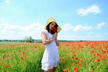 Jeune Femme Brune En Robe Blanche Qui Se Tient Dans Un Champ De Coquelicots Et Cueille Un Bouquet De Fleurs De Coquelicots Vue De Face