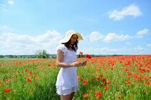 Jeune Femme Brune En Robe Blanche Qui Se Tient Dans Un Champ De Coquelicots Et Cueille Un Bouquet De Fleurs De Coquelicots Vue De Profil 5