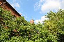 Clock Tower Of A Red Church In Kloster Neuendorf - Trees And Bushes In The Foreground