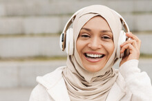 Middle Eastern Woman In Hijab Listening Music With Wireless Headphones