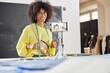 Leinwandbild Motiv Smiling African-American teacher shoots tutorial for fashion design class at table