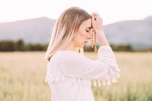 Calm Female Praying With Cross In Field