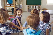 Team Of School Children Joining Hands Standing In Circle In Modern Classroom. Bunch Of Cute Kids Having Bonding Moment With Friends, Feeling United And Supported. Peer Group, Community, Unity Concept