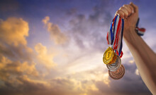 Different Medals In The Blue Sky In The Sun In Hand - Victory Concept