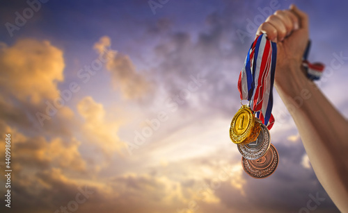 Foto different medals in the blue sky in the sun in hand - Victory Concept