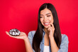 Leinwandbild Motiv Portrait of attractive trendy hungry cheerful girl holding doughnut wish want biting nail isolated over bright red color background