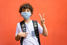 Cute Schoolboy With Backpack And Face Mask Isolated On A Vivid Background Making V, Victory Gesture. Back To School In Coronavirus Time Concept.